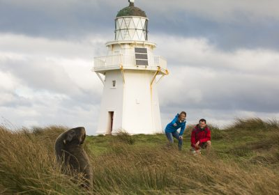 Waipapa Point Lighthouse with sea lion and people